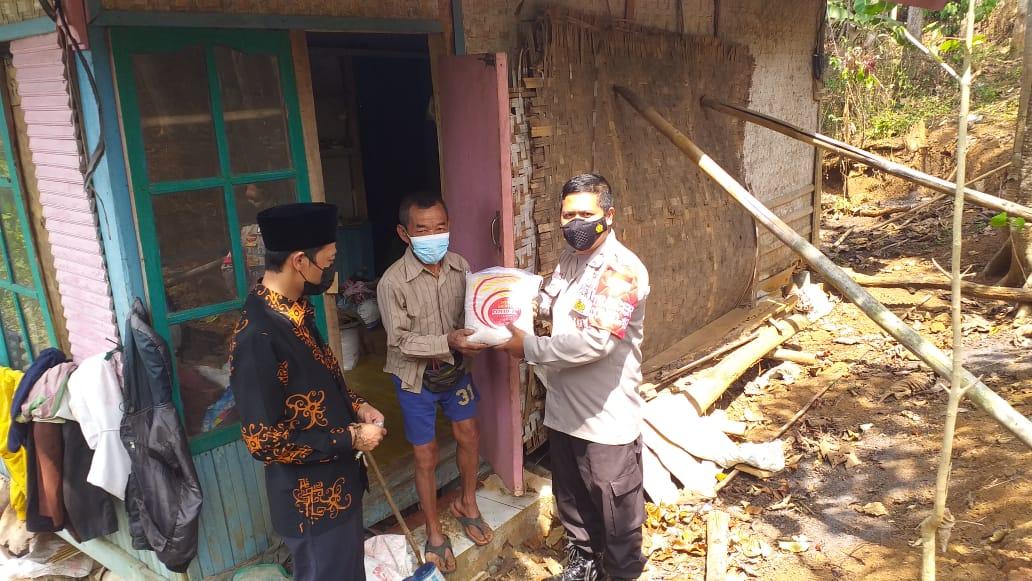 Anggota Polsek Cibugel saat menyerahkan bantuan beras 5 kg kepada warga terdampak covid-19